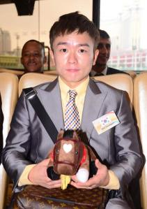 Seo Seung Un poses with a doll and some Louis Vuitton in Macau yesterday (Pic: Macau Jockey Club)