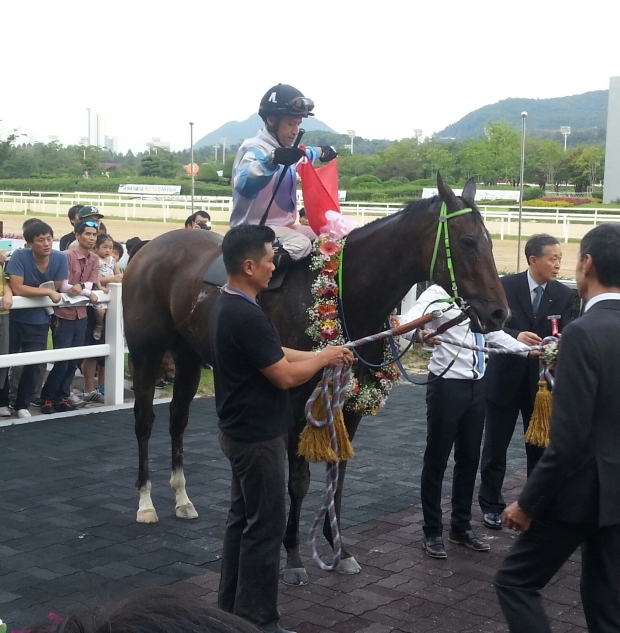 El Padrino and David Flores fly the flag in the Winner's Circle